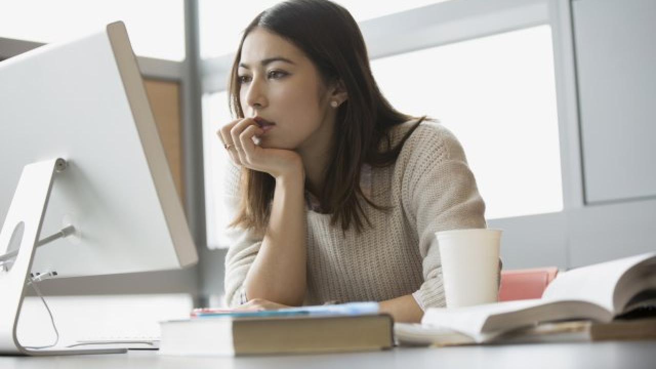 Woman staring at computer leaning face on hand